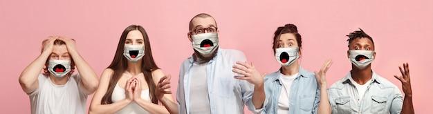 ピンクの珊瑚の壁に保護フェイスマスクを身に着けている驚いた、幸せな人々、女性と男性のグループ。
