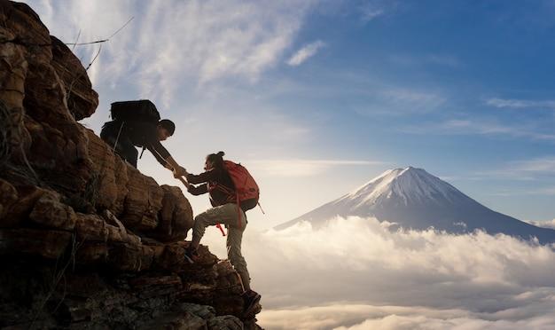 아시아 하이킹의 그룹은 햇빛 산에서 서로 실루엣을 도와줍니다.