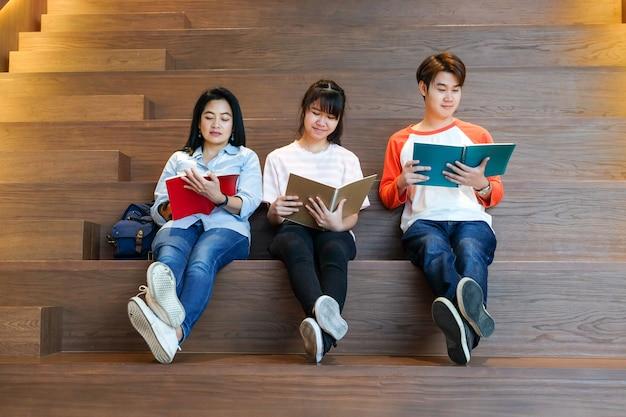 Группа студентов азии и преподаватель, читающих свои книги, сидя на лестнице библиотеки, образования и людей концепции фона