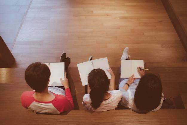 Группа студентов азии, держа пустые записные книжки, сидя на лестнице библиотеки с копией пространства в старинных тонах, образования и людей концепции фона