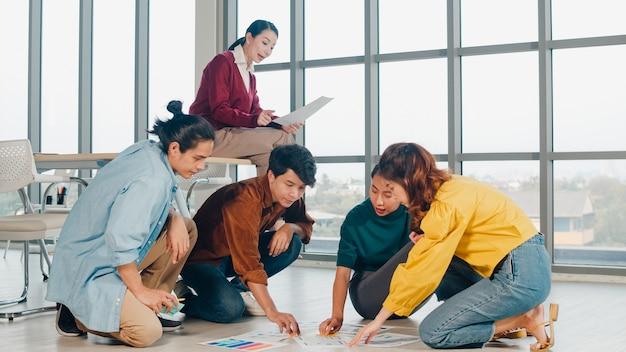 オフィスの床にレイアウトされたビジネスブレーンストーミング会議のアイデアモバイルアプリケーションソフトウェアデザインプロジェクト計画を議論するカジュアルな服装でアジアの若い創造的な人々のグループ。同僚のチームワークの概念。