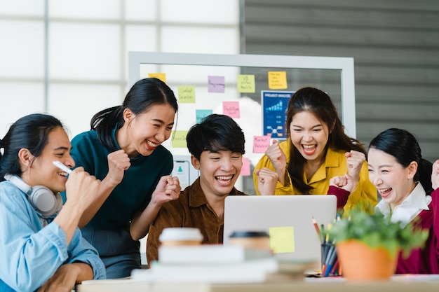 ビジネスを論議するスマートカジュアルウェアのアジアの若い創造的な人々のグループは、オフィスでの契約または合意に署名し、幸せな気持ちに対処した後、5を与えることを祝います。同僚のチームワークの概念。