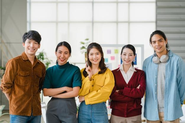 笑顔と腕を組んでスマートカジュアルなアジアの若い創造的な人々のグループは、創造的な仕事場で交差しました。多様なアジアの男性と女性がスタートアップで一緒に立ちます。同僚のチームワークの概念。