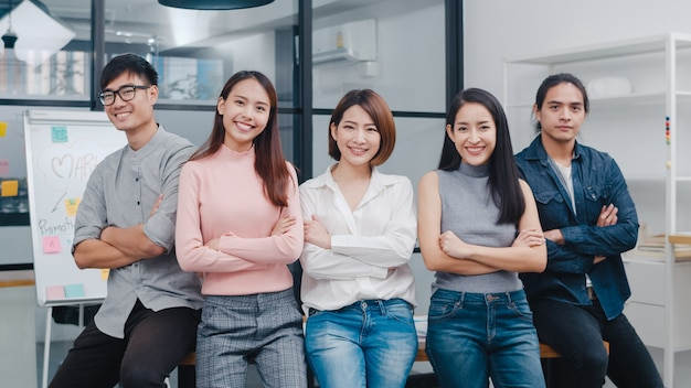 スマートカジュアルなアジアの若いクリエイティブな人々のグループは、クリエイティブなオフィスの職場で笑顔と腕を組んでいます。