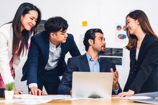 新しいプロジェクトとのアジアのビジネス会議のグループ。ラップトップで計画している創造的なビジネスマン