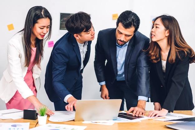 新しいスタートアッププロジェクトとのアジアのビジネスミーティングのグループ。創造的なビジネスの人々はラップトップを使用します
