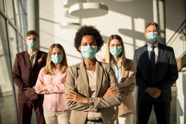 コロナウイルスによる感染を防ぐためにオフィスで立っているマスクを着用してアジアのビジネス人々のグループ