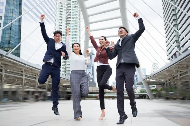 아시아 사업 사람들의 그룹 판매가 계속 된 후 성공 행복 하 게 뛰어 오르고있다.