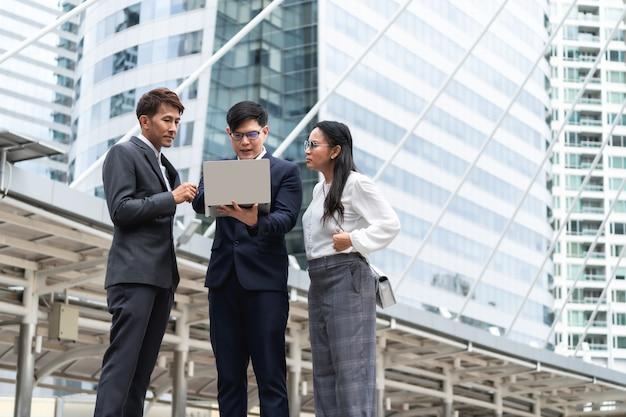 Группа азиатских деловых людей, работающих и обсуждающих со своим зрелым коллегой и использующих ноутбук на открытом воздухе в столице