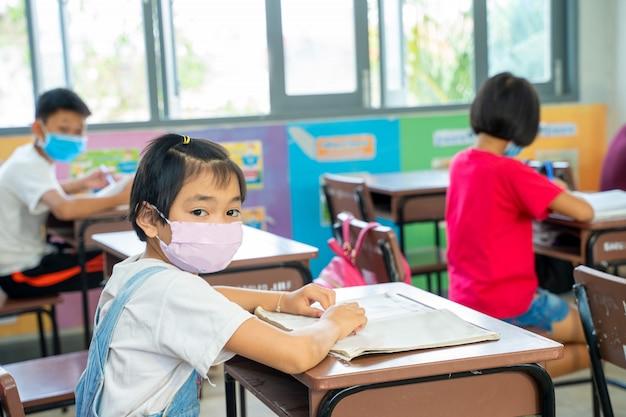 教室、小学校、社会的分散、コロナウイルスの机に座っているcovid-19から保護するために防護マスクを身に着けているアジアの子供たちのグループは、世界的な緊急事態になりました。