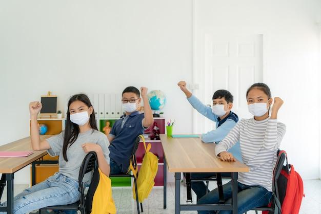 Группа азиатских учеников начальной школы в гигиенической маске