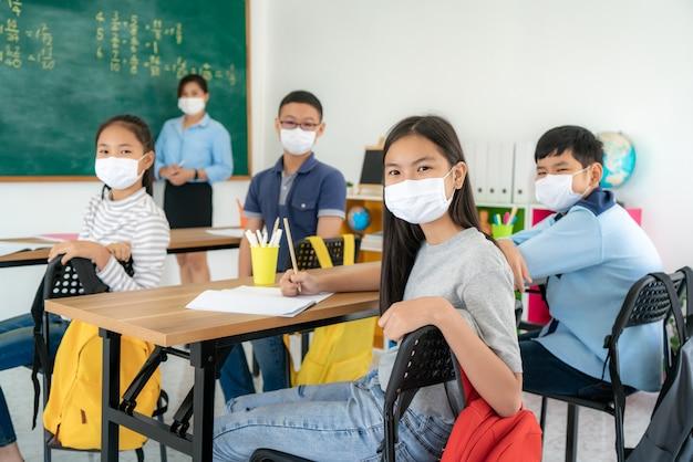 防護マスクを身に着けているアジアの小学生のグループ