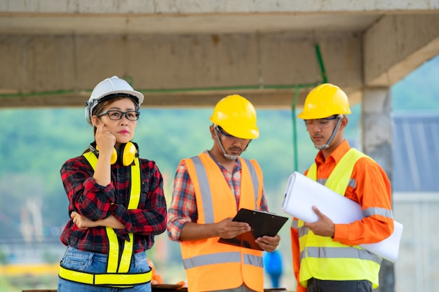 建設現場の建物の下でアジアのエンジニアまたは建築家と建設労働者のグループ。