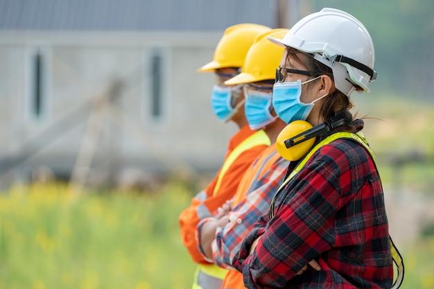 建設現場でヘルメットの安全性を備えたcovid-19から保護するために保護マスクを着用しているアジアのエンジニアのグループ、