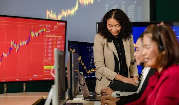 아시아 여성 고객 서비스 운영자 그룹은 마이크 헤드셋을 착용하고 매일 그래프 차트 컴퓨터 모니터 화면 앞에서 웃고 고객과 온라인으로 주식 시장을 사고 팔고 있습니다.
