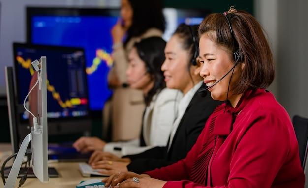 아시아 여성 고객 서비스 운영자 그룹은 매일 그래프에서 웃는 마이크 헤드셋을 착용합니다.