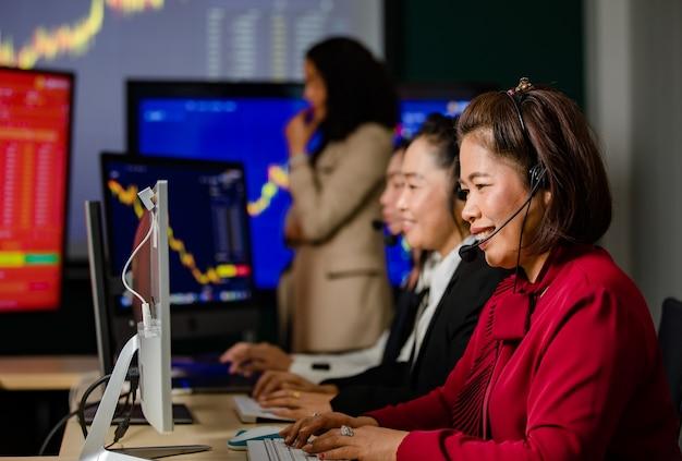 아시아 여성 고객 서비스 운영자 그룹은 매일 앞에서 미소 짓는 마이크 헤드셋을 착용합니다.