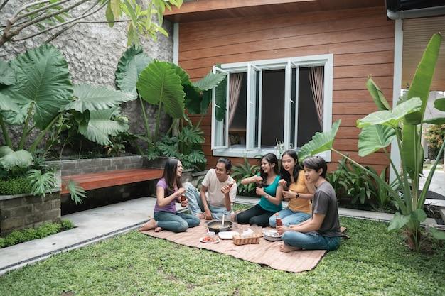 뒷마당에서 먹고 마시는 동안 재미 아시아 친구의 그룹