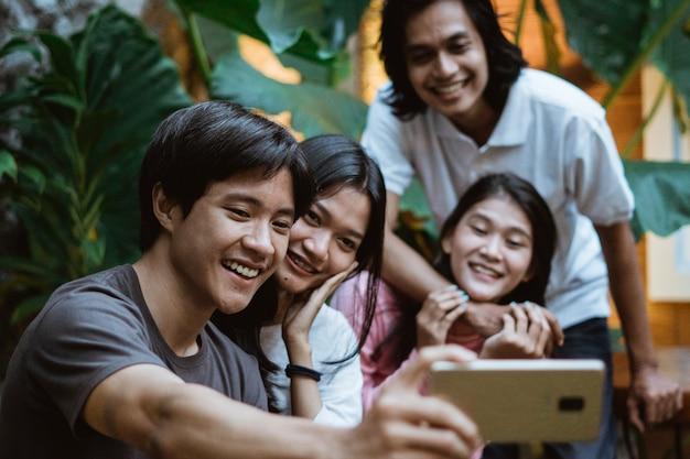 아시아 친구 그룹은 벤치에 앉아있는 동안 정원에서 스마트 폰을 사용하여 화상 통화를