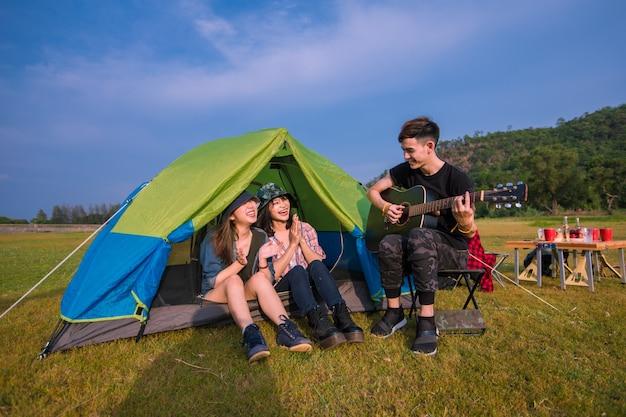 Группа азиатских друзей туриста пьет и играет на гитаре вместе со счастьем летом во время кемпинга возле озера на закате