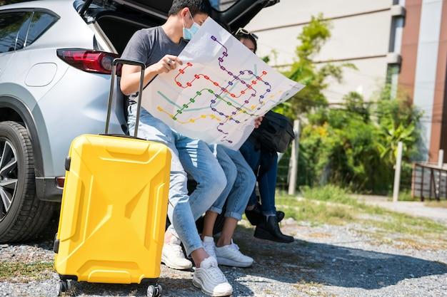 Группа азиатских друзей в маске сидит на заднем багажнике внедорожника, чтобы проверить карту путешествия. молодые мужчины и женщины едут в отпуск. заблудитесь о месте путешествия.