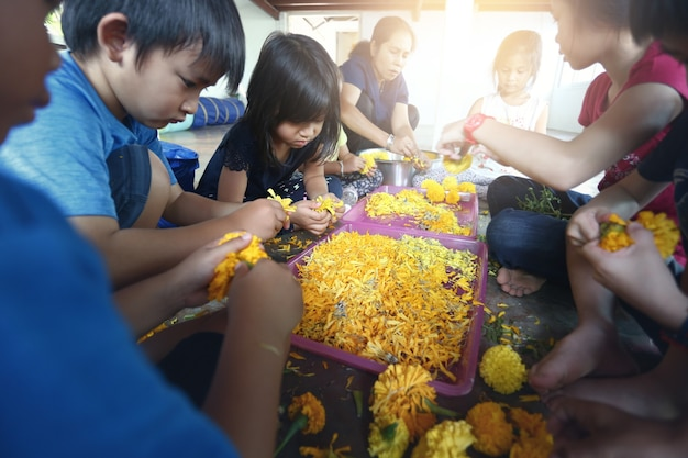 꽃꽂이를 배우고 집에서 즐거운 시간을 보내는 아시아 아이들.