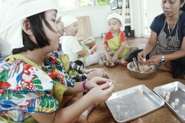음식을 준비하고 집에서 즐거운 시간을 보내는 아시아 아이들.