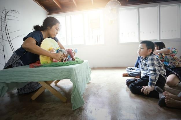 아시아 어린이 그룹이 앉아서 손으로 만든 월도프 인형으로 선생님의 이야기를 듣습니다.