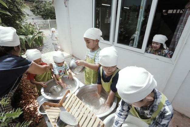 아시아 아이들이 함께 설거지를 하고 집에서 즐거운 시간을 보내고 있습니다.