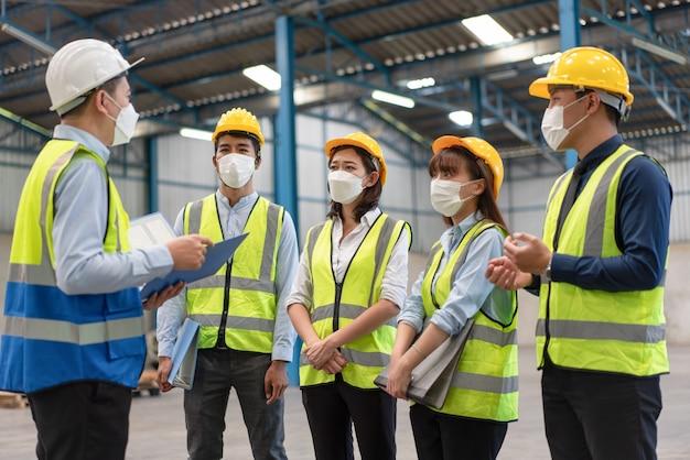 아시아 남성 및 여성 엔지니어 그룹은 공장 산업에서 헬멧 안전을 갖춘 마스크를 착용합니다.