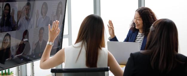 아시아의 성숙한 여성 여성 사업가 직원들이 정장을 입고 앉아 웃고 있는 모습을 보고 큰 모니터 화면 인사말을 보고 원격 회의에서 다문화 동료들에게 인사를 전합니다.