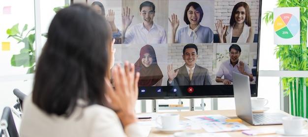 Группа азиатских зрелых женщин-предпринимательниц офицерский штаб в официальном костюме сидит, улыбаясь, смотрит на экран большого монитора, приветствует, передает привет многонациональным коллегам на телеконференции.