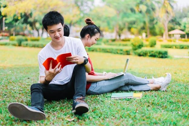 アジアの学生のグループは、庭の草の上で同時に本を読むつもりです。