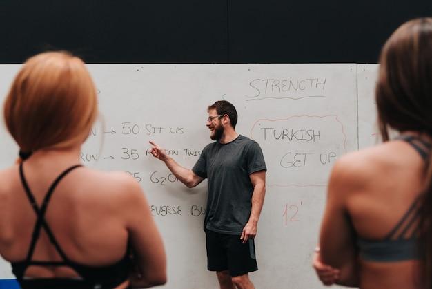 코치가 함께 할 운동 루틴을 설명하는 동안 코치의 말을 듣고있는 운동 선수 그룹.