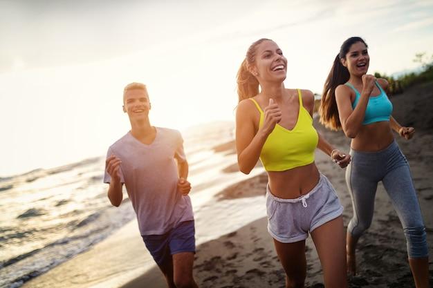 바다 앞을 달리는 운동 선수 그룹. 야외에서 함께 훈련하는 운동복을 입은 친구들.