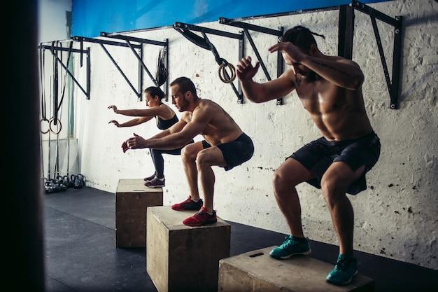 Группа спортивных людей прыгают через некоторые коробки в тренажерном зале кросс-тренировки