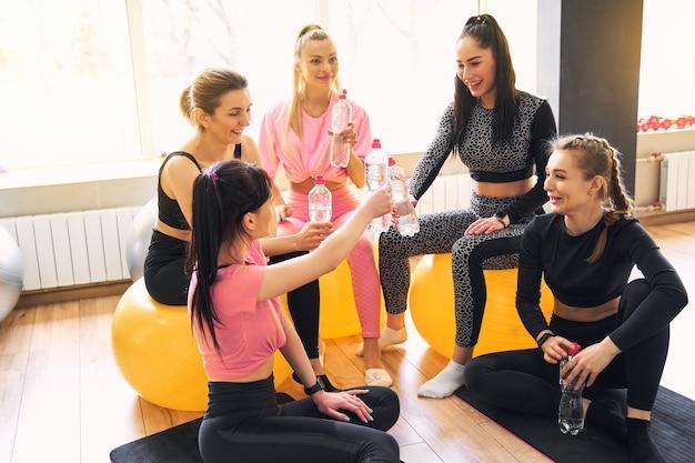 스포츠 훈련 중 휴식 시간에 재미 운동 여성 그룹 신선한 물을 마셔