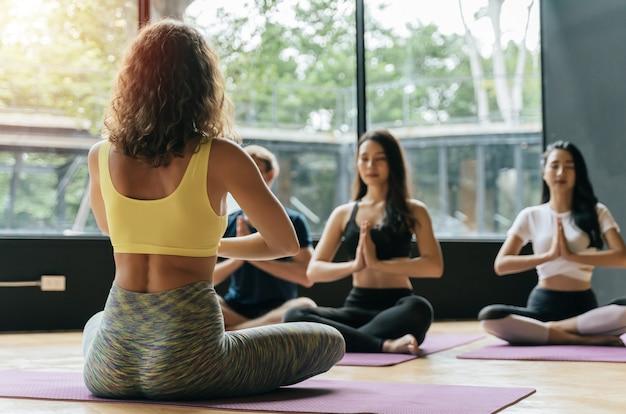 Группа спортивных молодых разнообразных культур спортивных людей, практикующих йогу