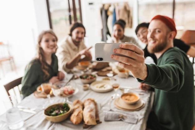 아늑한 카페에서 시간을 보내는 음식으로 가득 찬 테이블에 앉아 매력적인 국제 친구의 그룹