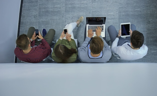 랩톱, tablet pc, 스마트 폰을 사용하여 바닥에 앉아 있는 매력적인 젊은 사람들의 그룹이 웃고 있습니다.