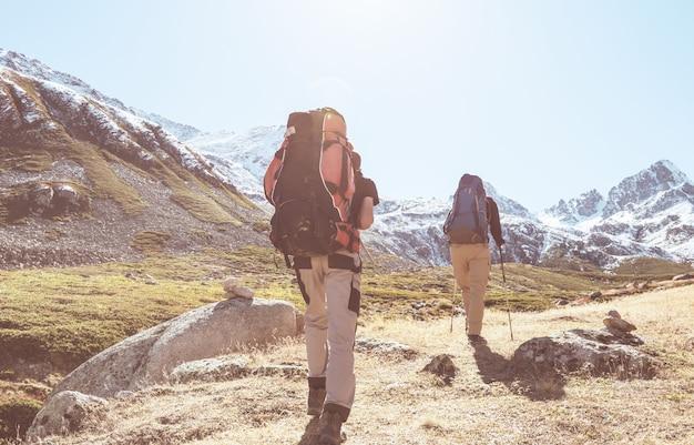 山でハイキングするバックパッカーのグループアウトドアアクティブライフスタイル旅行冒険休暇旅の自由夏の風景ハイキングのコンセプト