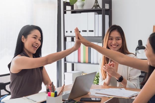 美しい幸せなアジアの女性のグループが集まり、オフィススペースでハイタッチをして、ビジネスのスタートアッププロジェクトについて話し合ったりブレインストーミングしたりします。