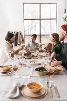 서로 이야기하는 음식으로 가득 찬 테이블에 앉아 아름다운 국제 친구의 그룹
