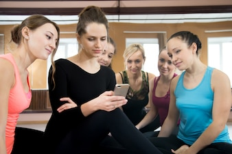 Group of beautiful sporty girls using mobile phone on break in sports gym