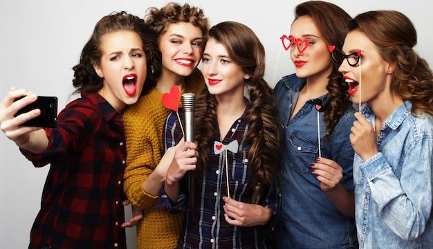 カラオケを歌う美しいスタイリッシュな流行に敏感な女の子のグループ