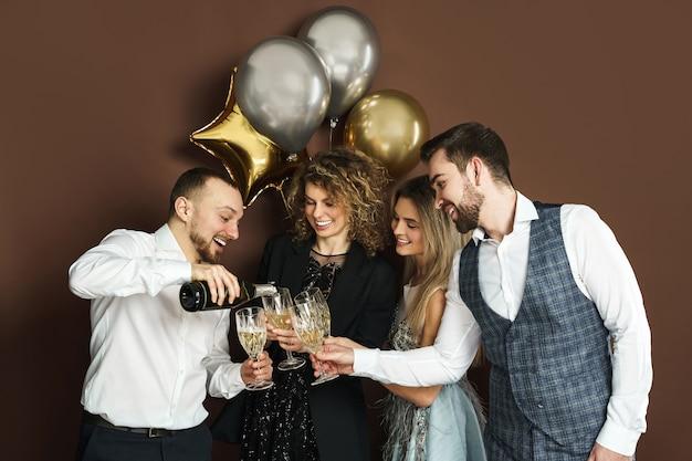 Группа красивых хорошо одетых людей, празднующих праздник или событие и пьющих игристое вино
