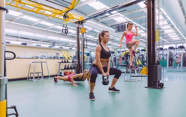 フィットネスセンターのクロスフィットサーキットで一生懸命トレーニングしている美しい女性のグループ