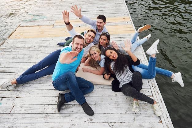 Группа красивых молодых людей на пирсе, удовлетворение друзей создает эмоциональную жизнь.