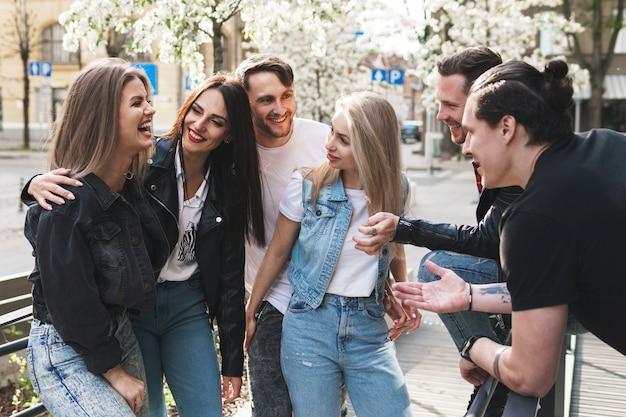 Группа лучших друзей веселится на улице. молодые люди рады видеть друг друга во время встречи.