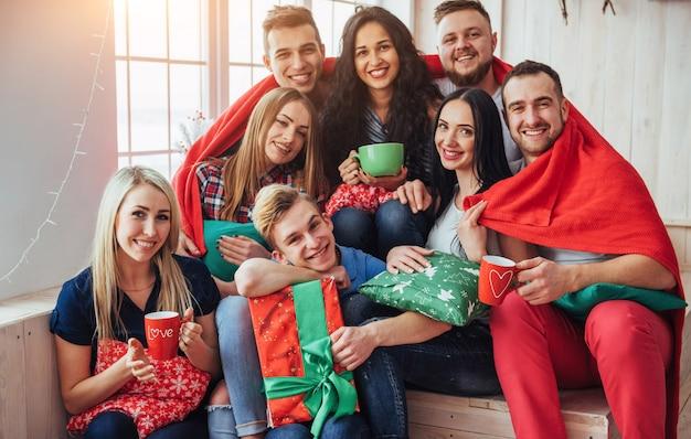 Группа лучших друзей на вечеринке. улыбающиеся и веселые люди сидят на лестнице за чашкой кофе, поздравляют с днем рождения, отличный подарок